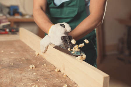 Professional carpenter grinding wooden plank with jack plane in workshop, closeup