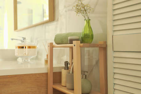 Shelving unit with toiletries in stylish bathroom interior