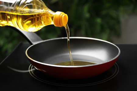 Pouring cooking oil from bottle into frying pan, closeup