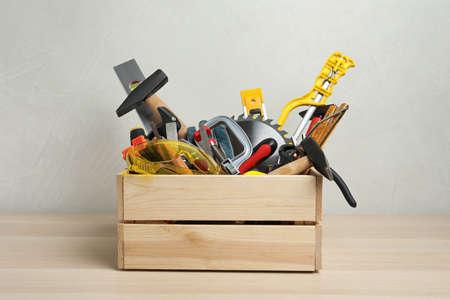 Caisse avec différents outils de menuisier sur table en bois Banque d'images