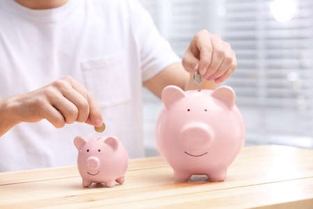 Man putting coins into piggy banks at wooden table, closeup Standard-Bild