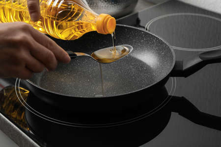 Woman pouring cooking oil from bottle into spoon, closeup Stock Photo