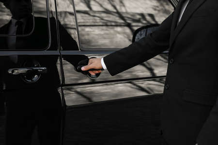 Driver opening door of luxury car, closeup. Chauffeur service