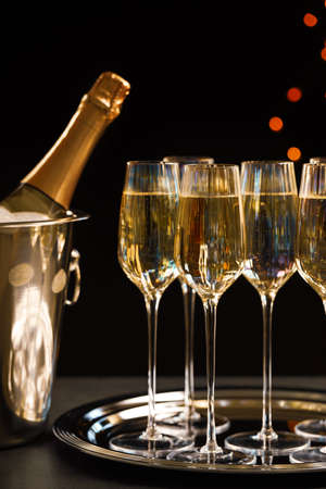 Glasses of champagne and ice bucket with bottle on grey table