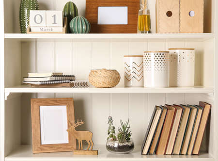 White shelving unit with books and different decorative elements