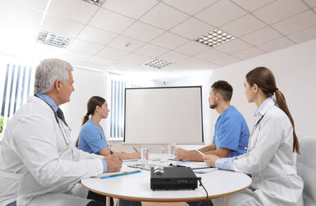 Team of doctors using video projector during conference indoors Stock Photo