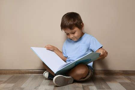 Cute little boy reading book on floor near beige wall