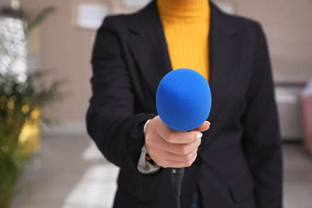 Professioneller Journalist mit modernem Mikrofon im Zimmer, Nahaufnahme