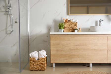 Elegante bagno moderno con mobile in legno vicino alla parete in marmo Archivio Fotografico
