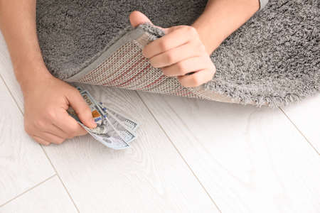 Man hiding money under carpet indoors, closeup. Financial savings