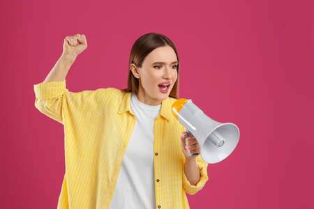 Emotional young woman with megaphone on pink background Stock Photo