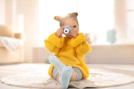 Little photographer taking picture with toy camera at home