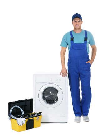 Reparador con caja de herramientas cerca de la lavadora sobre fondo blanco. Foto de archivo