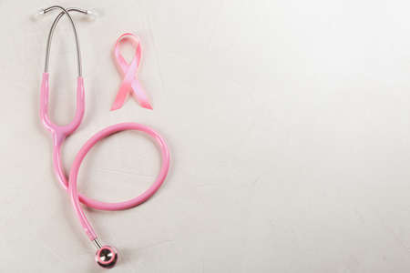 Pink ribbon and stethoscope on light grey stone background, flat lay with space for text. Breast cancer concept