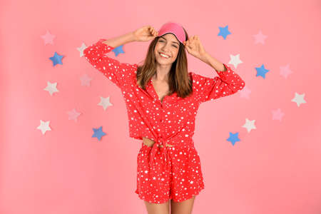 Beautiful woman wearing pajamas and sleep mask on pink background. Bedtime