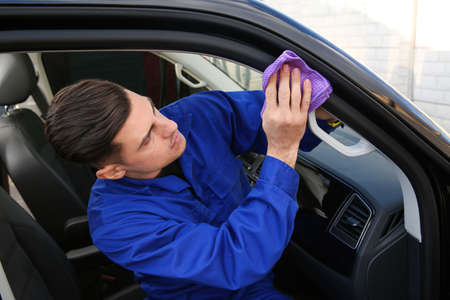 Car wash worker cleaning automobile with rag outdoors Archivio Fotografico