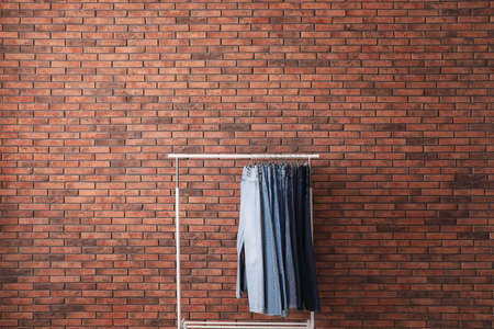 Rack with stylish jeans near brick wall