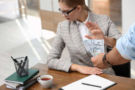 Businesswoman refuses to take bribe money at table in office