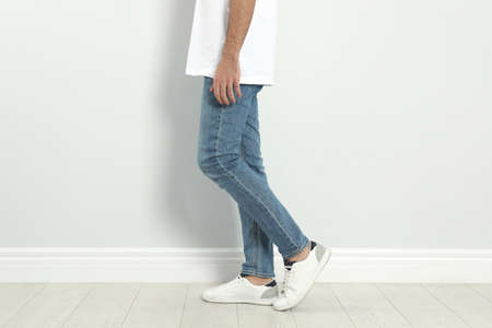 Young man in stylish jeans near light wall, closeup