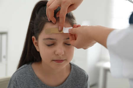 Doctor putting sticking plaster onto girl's forehead indoors