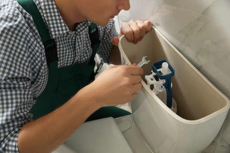 Professional plumber repairing toilet in bathroom, closeup