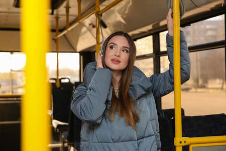 Woman listening to audiobook in trolley bus Imagens