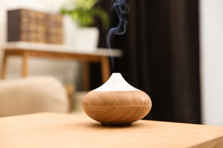Aroma oil diffuser on wooden table at home. Air freshener Stock fotó