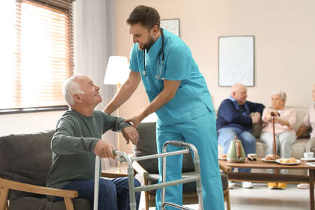 Medical worker taking care of elderly man with walker in geriatric hospice