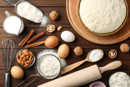 Dough and ingredients for pastries on wooden table, flat lay Stockfoto