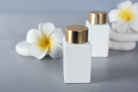 Cosmetic products, spa stones and tropical flowers on light grey table