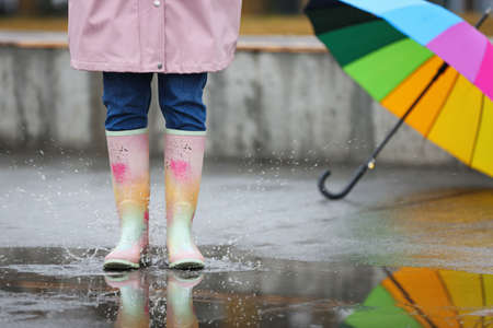 Woman in rubber boots walking outdoors on rainy day, closeup