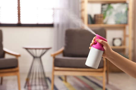 Woman spraying air freshener at home, closeup