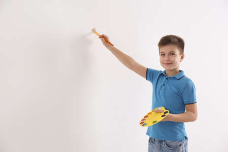 Little child painting on white wall indoors. Space for text