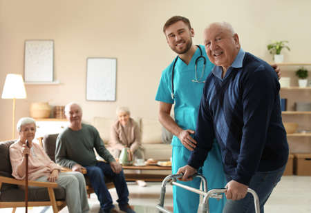 Care worker helping to elderly man with walker in geriatric hospice