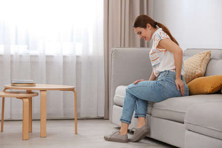 Young woman suffering from hemorrhoid on sofa at home