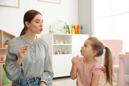 Speech therapist working with little girl in office