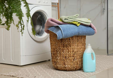 Wicker basket with laundry, detergent and washing machine in bathroom