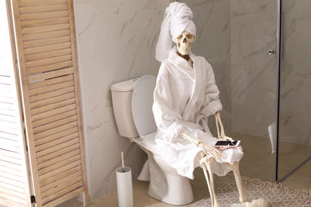 Skeleton in bathrobe with mobile phone sitting on toilet bowl Фото со стока