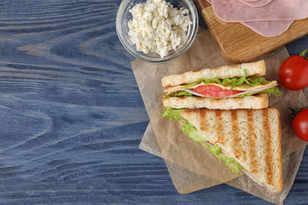 Tasty sandwich with ham on blue wooden table, flat lay. Space for text