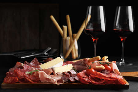 Tasty prosciutto with other delicacies served on black table Reklamní fotografie