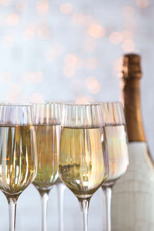 Glasses of champagne and bottle against blurred lights, closeup