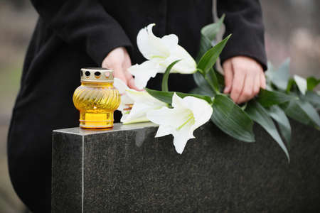 Woman holding white lilies near black granite tombstone with candle outdoors, closeup. Funeral ceremony