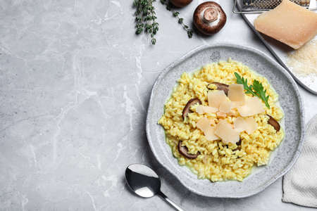 Delicious risotto with cheese and mushrooms on grey marble table, flat lay. Space for text