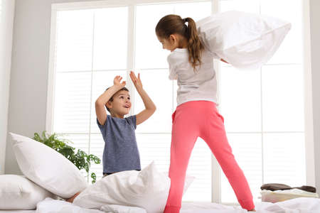 Happy children having pillow fight in bedroom