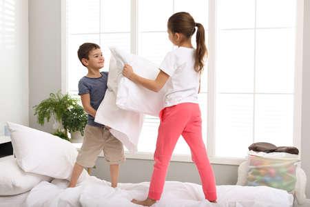 Bambini felici che litigano con i cuscini in camera da letto Archivio Fotografico