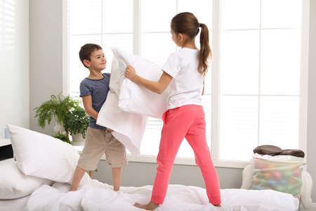 Niños felices con pelea de almohadas en el dormitorio Foto de archivo