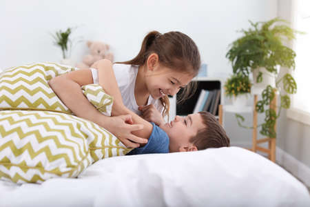 Happy children playing with pillows in bedroom Stock Photo