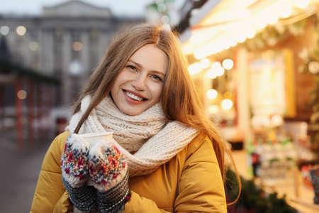 Mujer feliz con vino caliente en la feria de invierno Foto de archivo