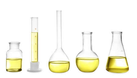 Different laboratory glassware with yellow liquid isolated on white