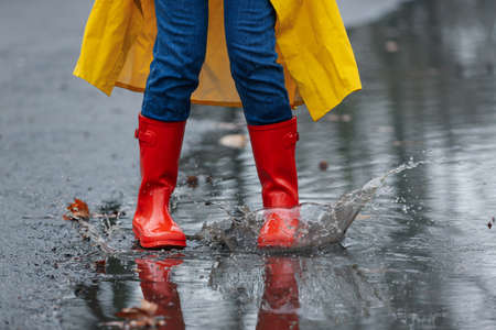 Woman splashing in puddle outdoors on rainy day, closeup